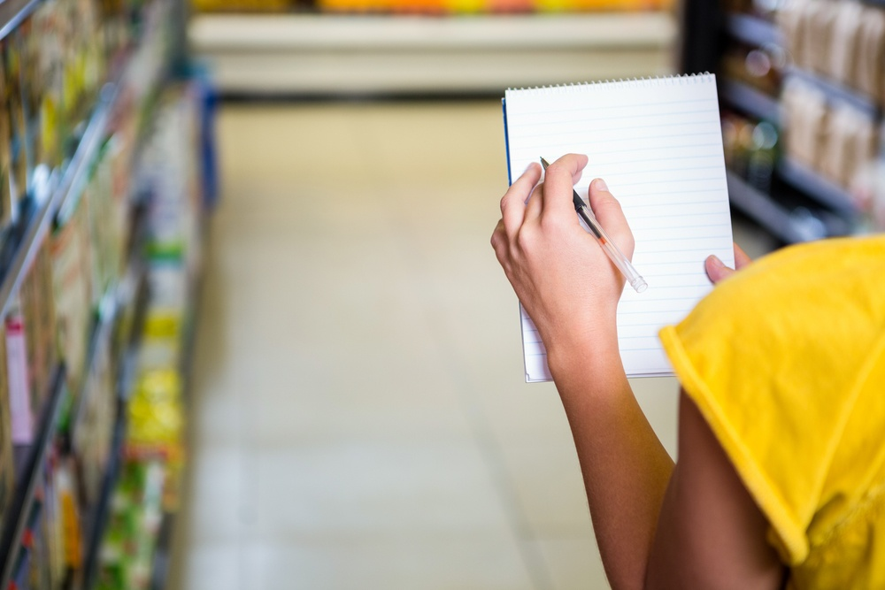 Cropped image of woman checking list at supermarket.jpeg